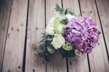 Foto de Big bouquet of fresh flowers, purple hydrangeas and white roses in a wicker basket on an old wooden board, vintage style - Imagen libre de derechos