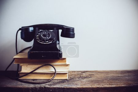 Photo for Black vintage rotary phone and books on rustic wooden table, on a white wall background - Royalty Free Image