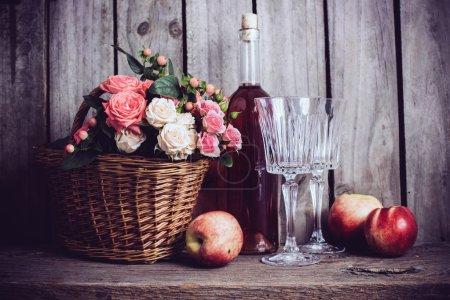 Photo pour Nature morte rustique, roses roses naturelles fraîches dans un panier en osier et une bouteille de vin de rose avec deux verres à vin et nectarines sur un vieux fond de panneau de grange en bois. Fleurs et fruits pour vintage - image libre de droit