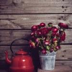 Постер, плакат: red flowers and enamel kettle