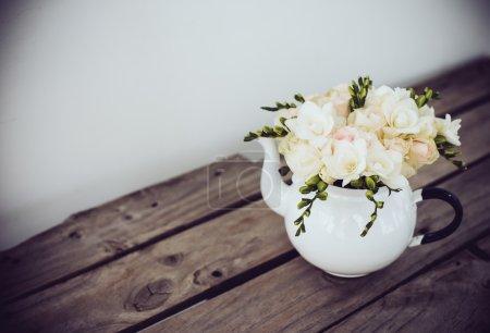 Photo pour Ravissant bouquet frais de roses blanches d'été et de freesias dans une théière vintage en émail sur une vieille planche de bois marron. Décoration intérieure de style rétro avec espace de copie - image libre de droit
