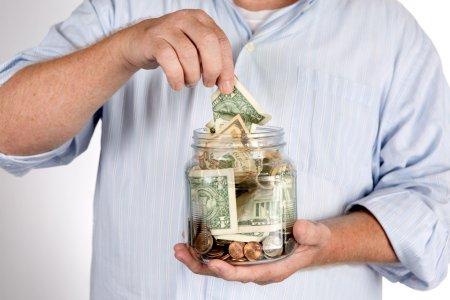Photo pour Retraité retire de l'argent de son épargne, banque, ou IRA compte tirelire concept . - image libre de droit