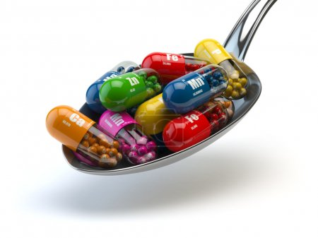 Capsules and pills on the spoon, isolated on white. Dietary supp