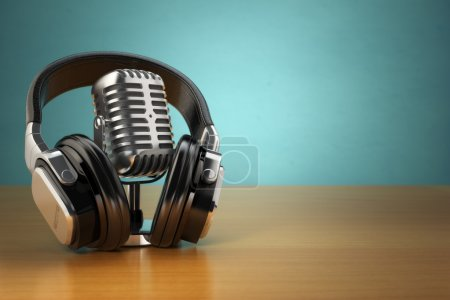Vintage microphone and headphones on green background. Concept a