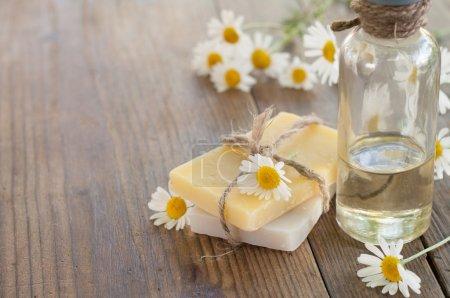Photo pour Barre de savon naturel fait main et camomille sur fond en bois. Concentration sélective . - image libre de droit
