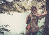 Woman hiker with backpack enjoying amazing mountain lake landscapes.