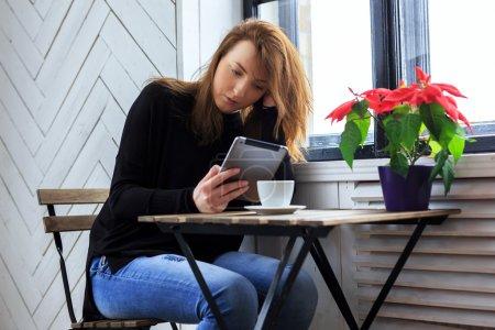 Photo pour Femme occasionnelle buvant du café et travaillant avec tablette pc - image libre de droit