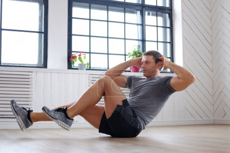 Photo for Middle age man in a grey t-shirt doing abs workouts on the floor - Royalty Free Image