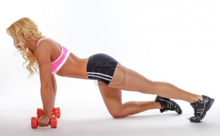 Female in sportswear exercising with dumbbells