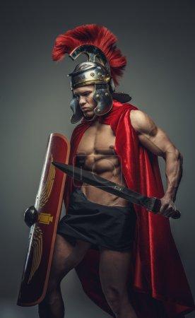 Photo pour L'homme musclé torse nu en armure romaine détient épée. - image libre de droit