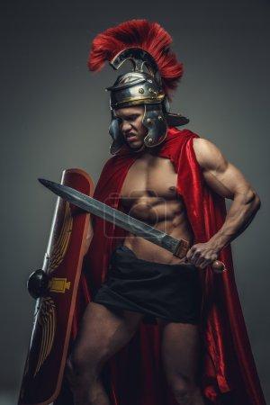 Photo pour Homme musclé torse nu dans une armure romaine tient l'épée . - image libre de droit