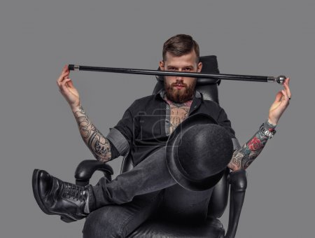Photo for Bearded tattooed freak guy with walking stick sitting isolated on a grey background - Royalty Free Image