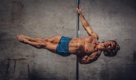 Shirtless man pole dancing