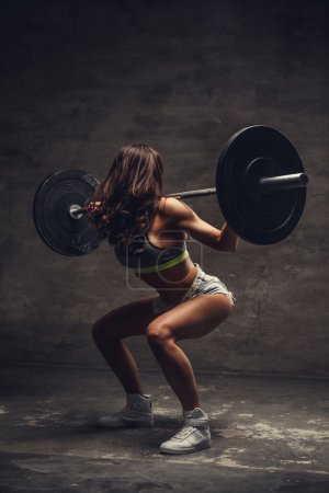 Female doing squats with barbell