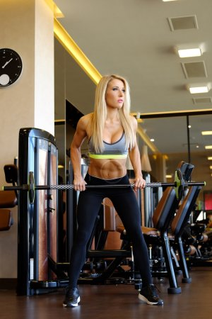 Sporty blond female exercising with barbell in a g...