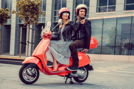 Male and female  on moto scooters.