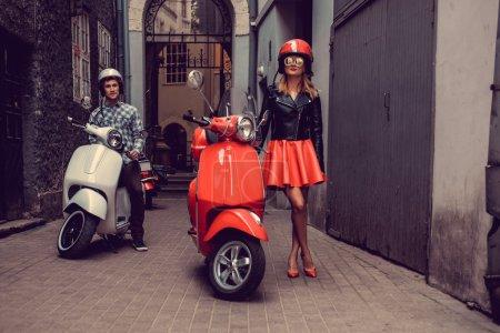 Photo pour Homme chic et à la mode femme blonde sur les scooters moto blanche et rouge avec le fond du centre - image libre de droit