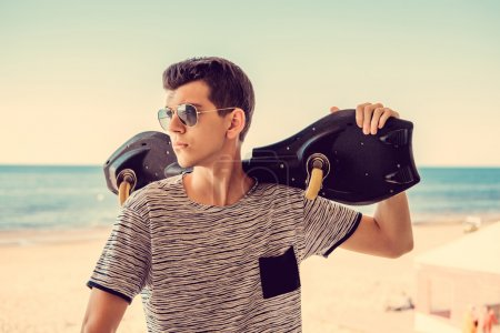 Attractive male holding skateboard