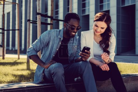 Photo for Afro american male and caucasian female with smartphone on a street. - Royalty Free Image