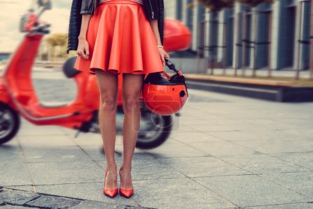 Female posing near motor scooter