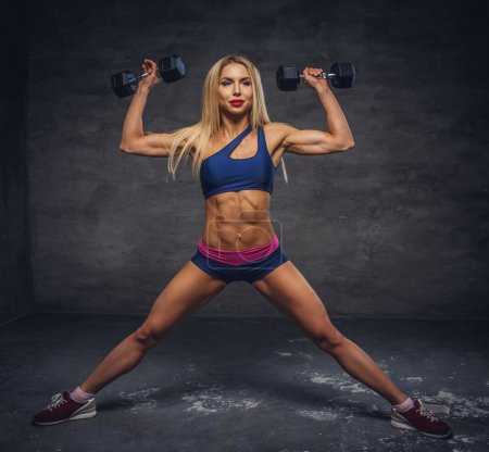 Photo for Sexy blond female in colorful sportswear doing workouts with dumbbells. - Royalty Free Image