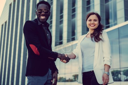 Photo for Caucasian female and black man handshake in a town. - Royalty Free Image