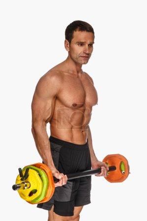 Photo pour Homme sans chemise d'âge moyen posant avec haltère colorée sur un fond clair . - image libre de droit