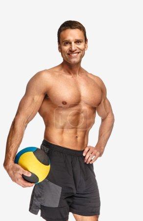 Photo pour Homme sportif torse nu tenant boule colorée sur fond blanc - image libre de droit