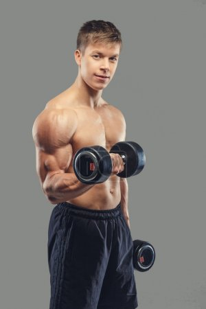 Photo for Shirtless muscular male doing biceps exercises with dumbbells on a grey background - Royalty Free Image