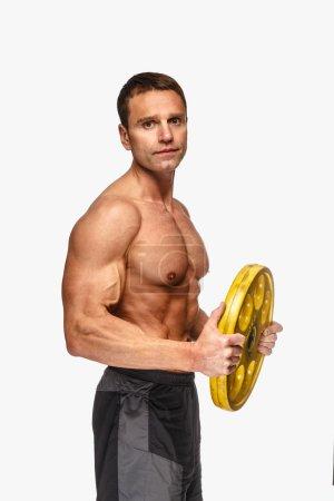 Photo pour Sporty torse nu mâle d'âge moyen tenant poids haltère jaune sur fond clair . - image libre de droit