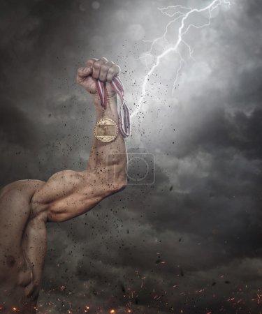 Photo pour Mâle main tenant médaille d'or contre le ciel dramatique - image libre de droit