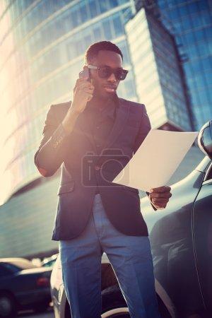 Photo pour Homme d'affaires africains parler de smartphone - image libre de droit