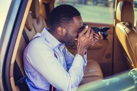 Photo for African american male in a white shirt shooting with dslr camera from car's back seat. - Royalty Free Image
