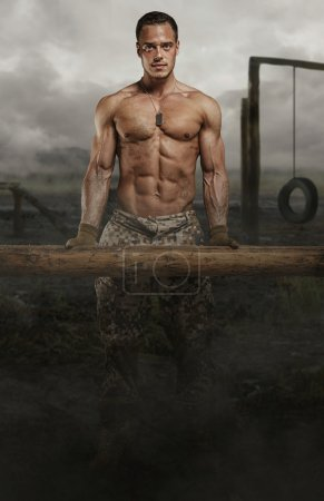 Photo for Shirtless soldier with wooden timber in a swampland. - Royalty Free Image