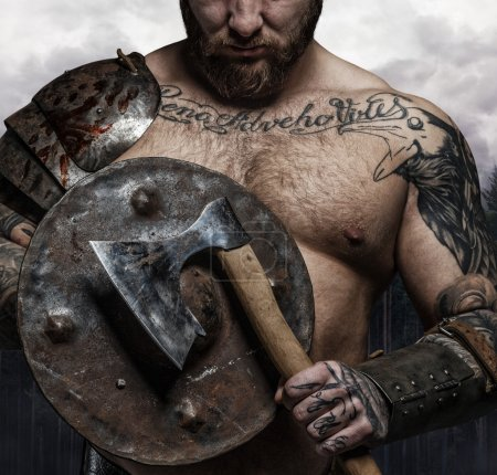 Tattooed male with viking shield and axe