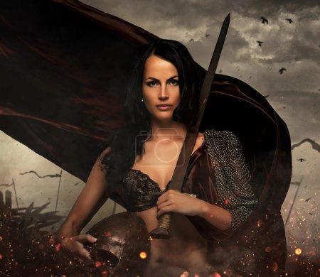 Female holding sword and helmet