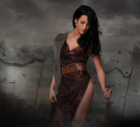 Sexy brunette female holding sword