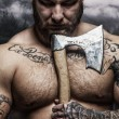 Portrait of tattooed male with viking axe