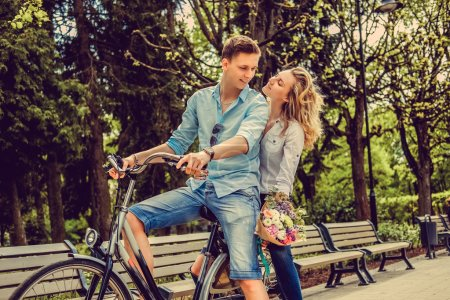 Joyfull couple posing on one bicycle.