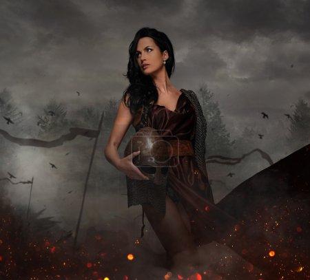 Attractive war queen holding helmet
