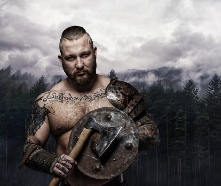 Brutal tattooed viking with axe and shield