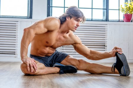 Athletic man warming up on a floor