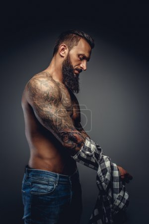 Tattooed male taking off his shirt
