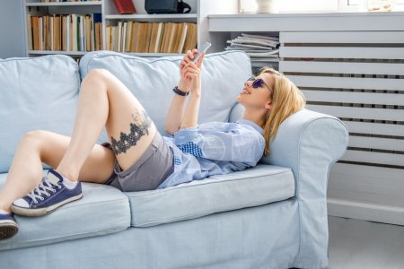 Female lying on a couch and using smartphone