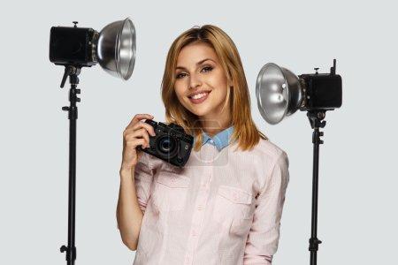 Photo pour Portrait studio de femme blonde positive avec appareil photo et équipement photo en arrière-plan - image libre de droit