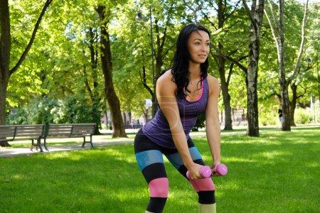 Female exercising with dumbbells in a park