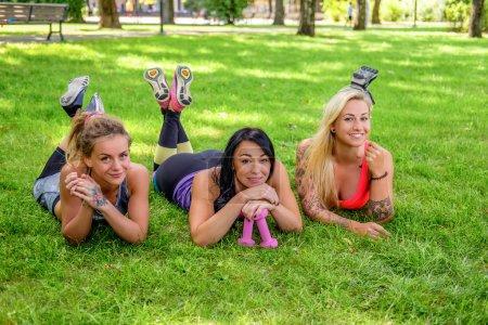 Athletic girls lying on green lawn