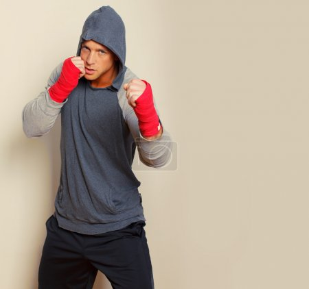 Young boxer is posing on a bright background