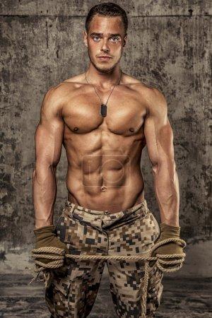 Photo pour Homme athlétique fort avec le corps nu dans armées pantalons gants de travail et de la corde sur le mur en béton - image libre de droit