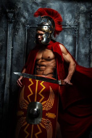 Photo for Roman warrior with muscular body holding sword and shield - Royalty Free Image